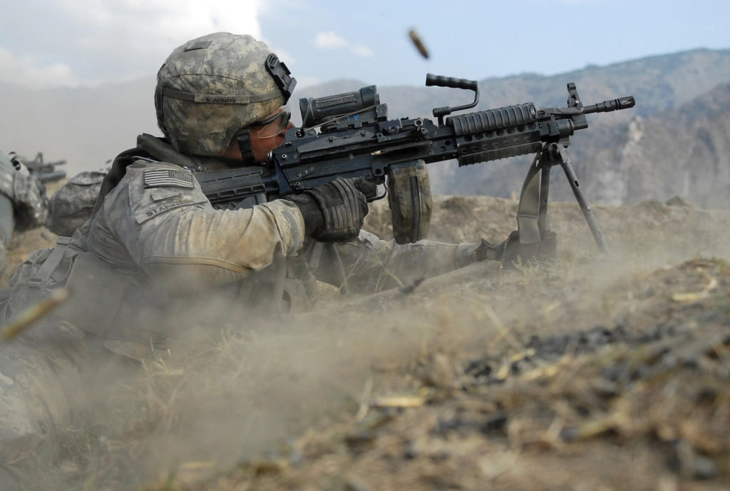 U.S. Army Pvt. John Stafinski, a native of Seville, Ohio, fires his M-249 squad automatic weapon during a three-hour gun battle with insurgent fighters in Kunar province, Afghanistan's Waterpur Valley, Nov. 3. Stafinski is an infantryman with Company C, 2nd Battalion, 12th Infantry Regiment, 4th Infantry Division, based out of Fort Carson, Colo.
